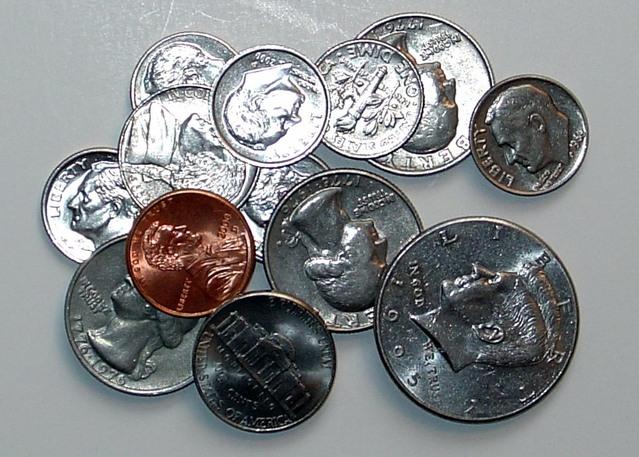 spousta kovových mincí na hromádce na stole