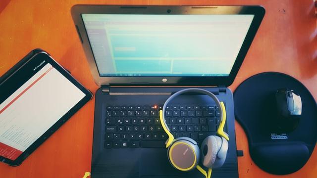počítač, sluchátka, myš a tablet na stole